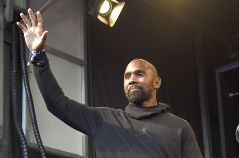Charles Woodson waving at people off camera.