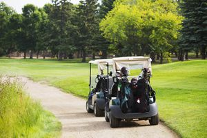 Two golf carts on the path next to a golf hole