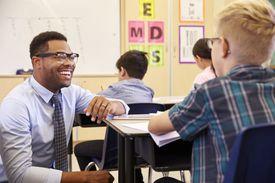 Smiling teacher kneeling beside elementary school pupil's desk