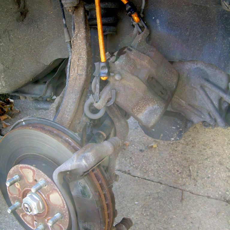 Brake caliper is suspended with a bungee cord.