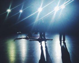 People Rehearsing On Illuminated Stage
