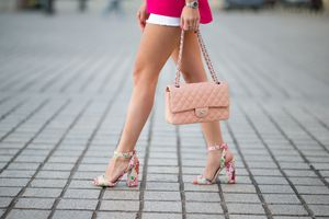 Woman's legs in high heel shoes and featuring a pink purse