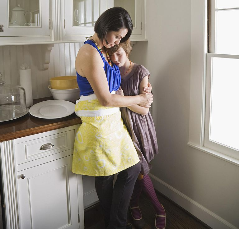 Mother comforting daughter in kitchen