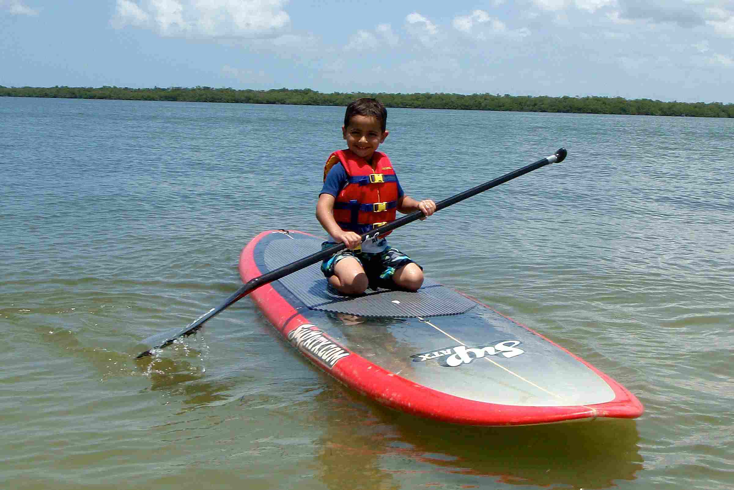 A Child Kneels on a Paddleboard