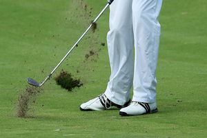 A golfer creates a divot with an iron shot from the fairway.
