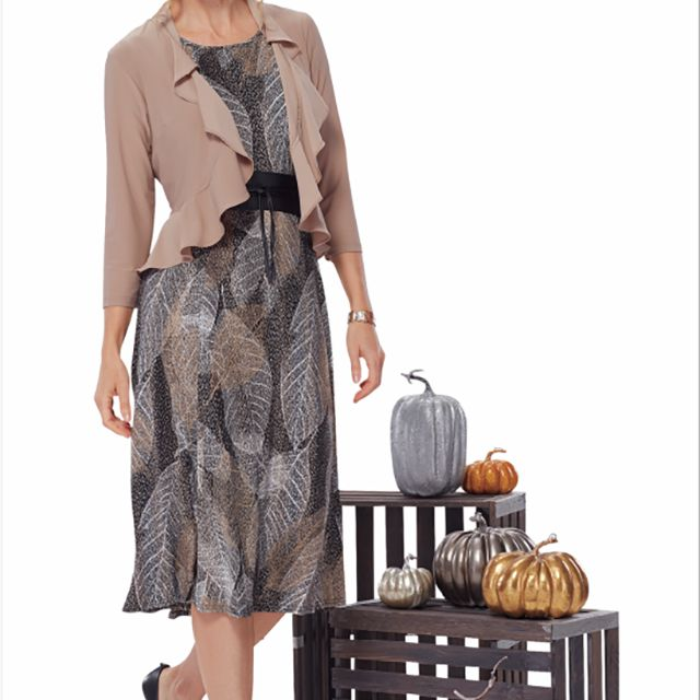 A woman wearing a dress standing by pumpkin decorations