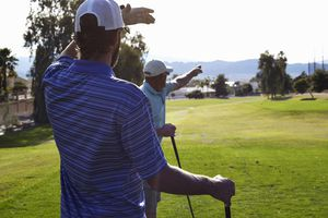 Two male golfers looking and pointing direction