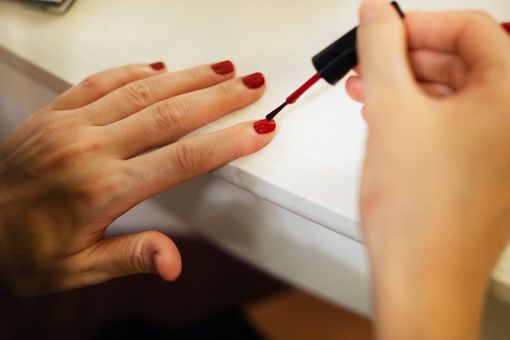 Young woman painting fingernails