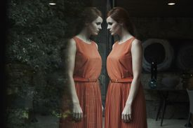 Woman wearing red dress looking at reflection of herself in glass window or door
