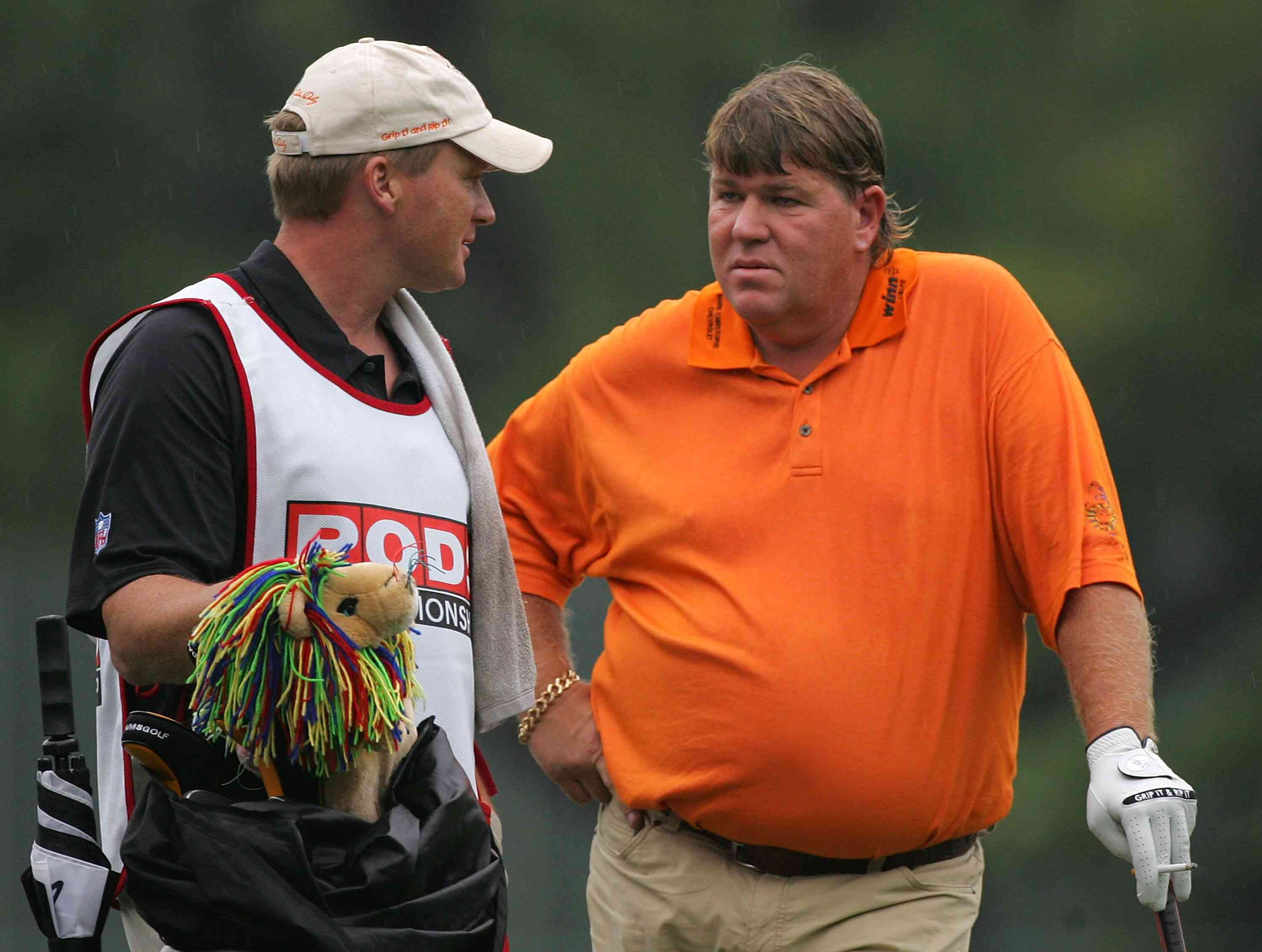 Head coach Jon Gruden of the Tampa Bay Buccaneers caddies for John Daly during the first round of the PODS Championship at Innisbrook Resort and Golf Club on March 6, 2008