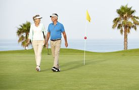 A man and a woman leaving a green after playing golf together