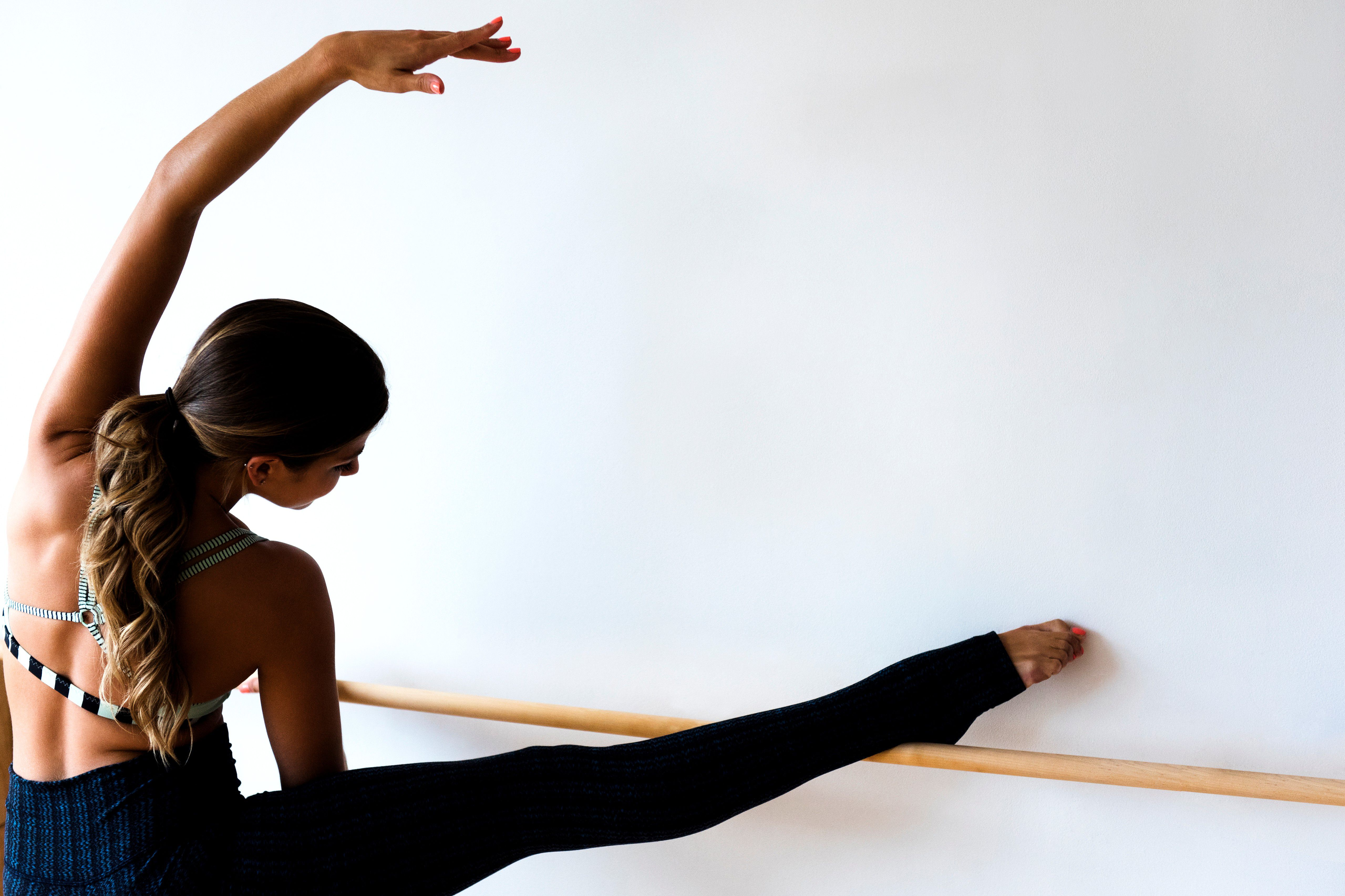 A dancer limbers up with a simple side stretch on the ballet barre