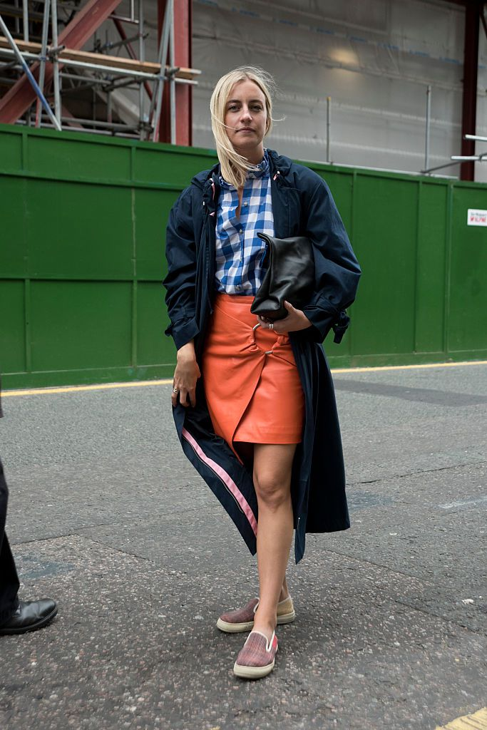 Street style woman in plaid shirt and leather mini skirt and trench coat and loafers