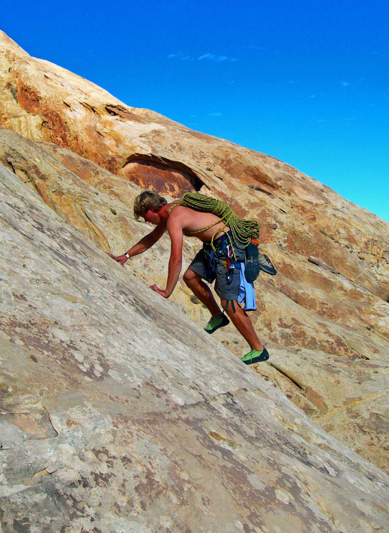 CJ Sidebottom scrambles up a sandstone slab at the San Rafael Swell, Utah.