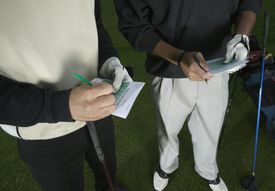Two men making notes on golf score cards