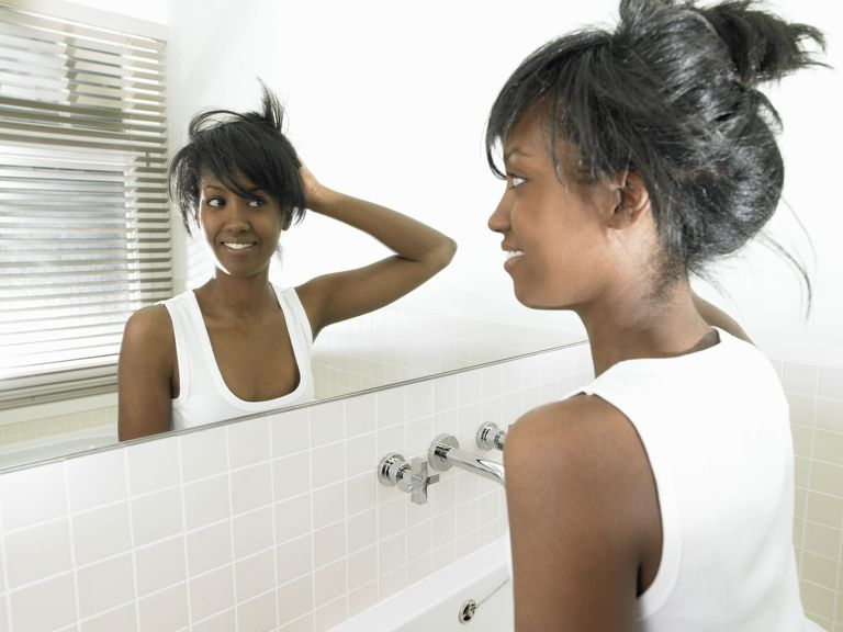 black woman looking at hair in mirror