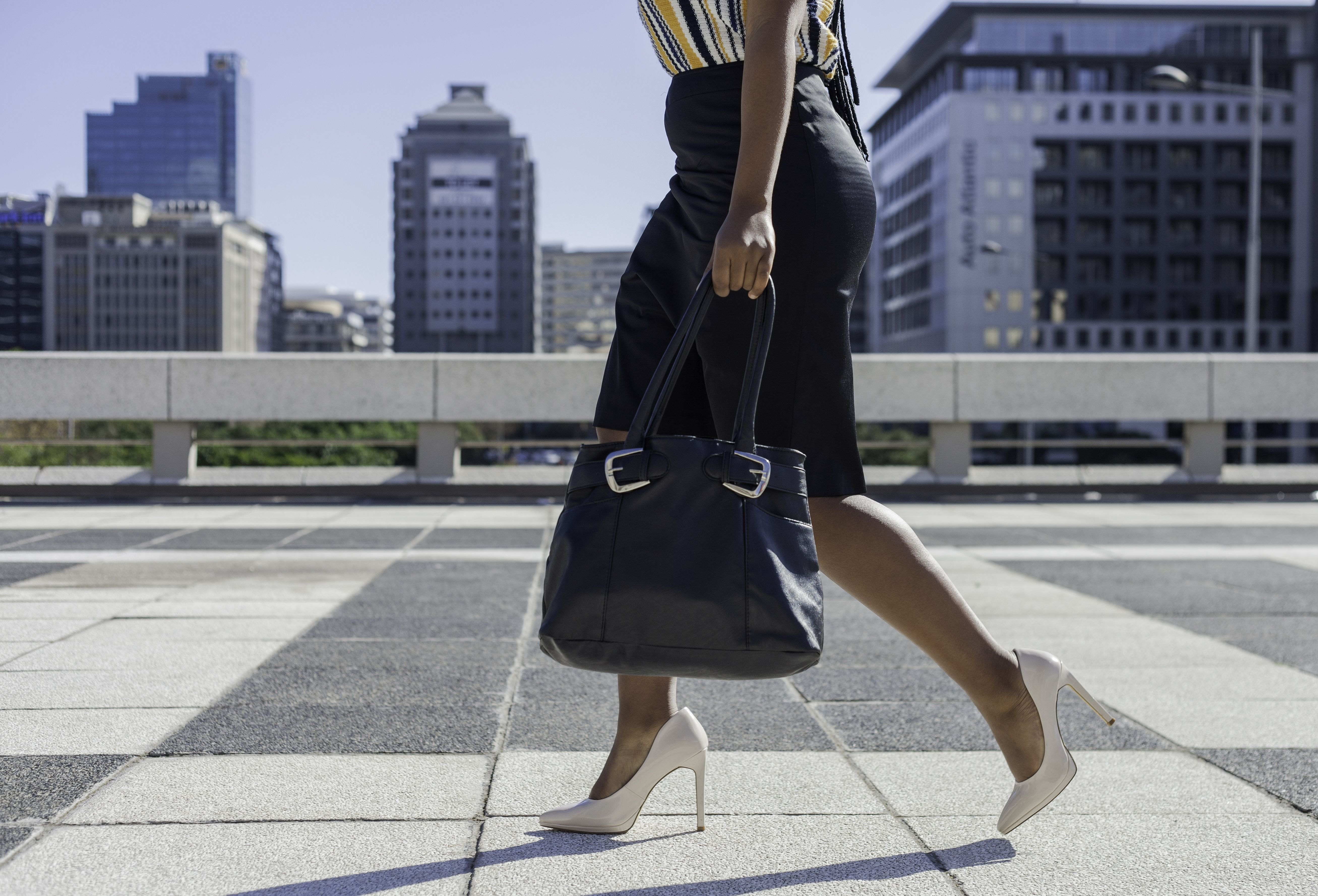 Businesswoman in high heels walking through the city with her purse in hand.