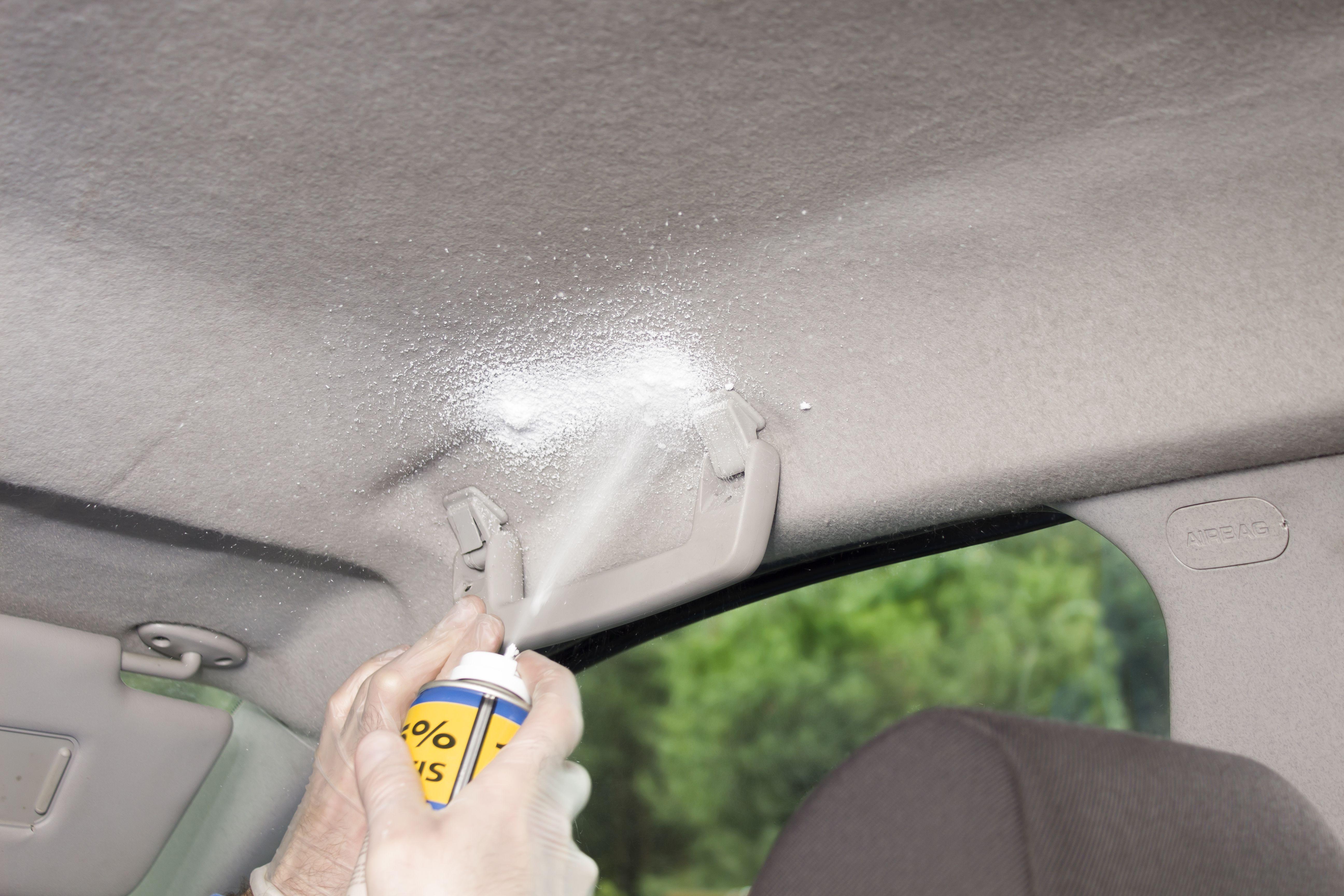 Applying upholstery foam to the headliner of a passenger car.