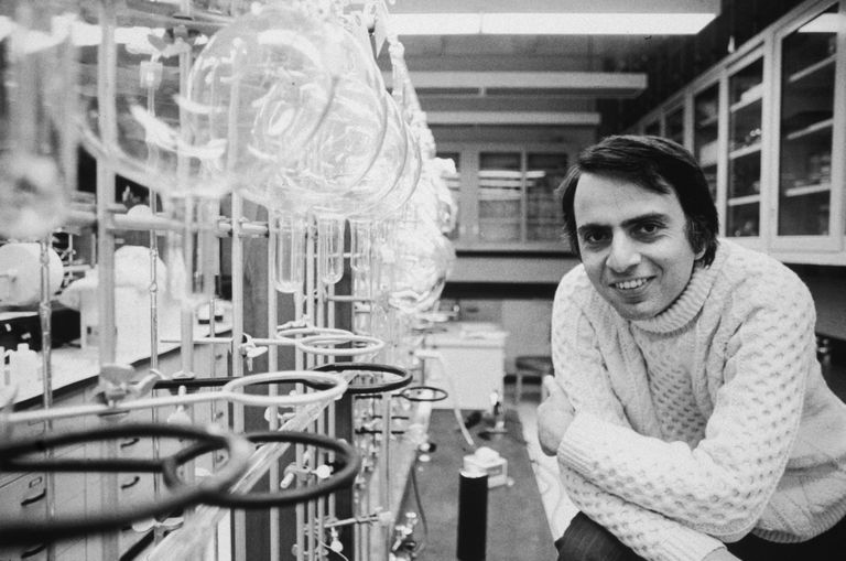 Carl Sagan smiling while leaning on arm in laboratory.