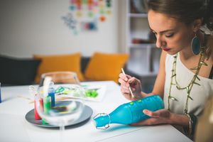 Woman painting design on glass bottle