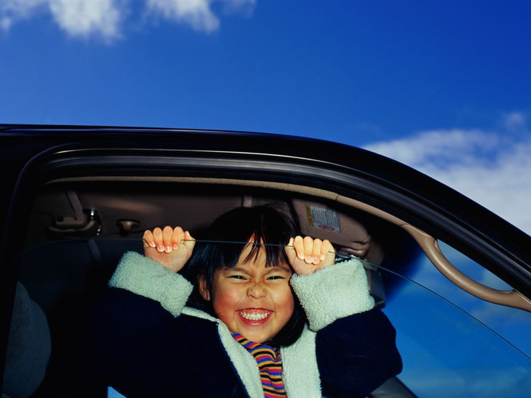 girl smiling behind partially-open car window