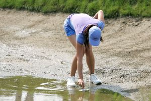 Michelle Wie picks up her ball after hitting into casual water in a bunker during the 2006 Women's US Open