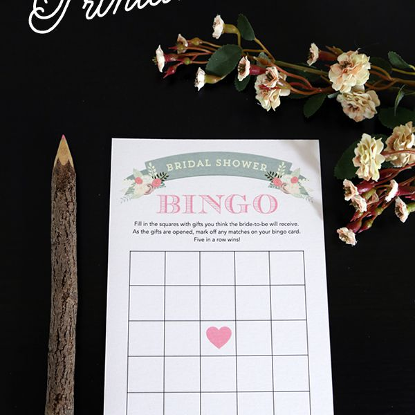 A bridal shower bingo card with a wooden pencil and flowers