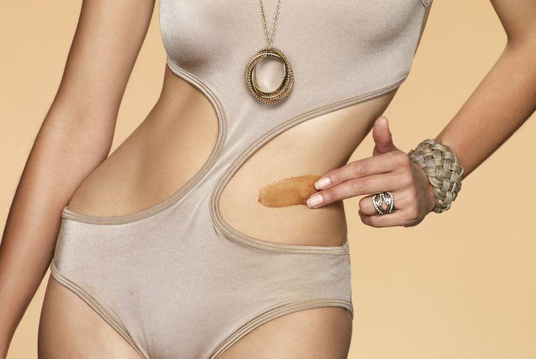 woman applying self-tanner to torso