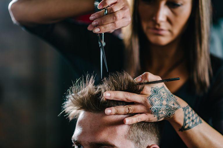 Tattooed woman cutting a man's hair