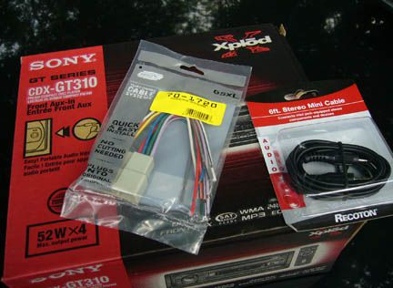 Car stereo in box, wiring kit, and iPod cable