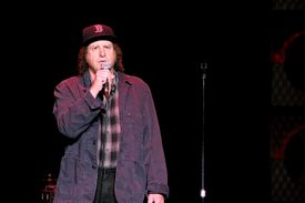 Steven Wright performing onstage with mic.