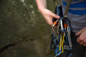 Rock climber preparing safety harness