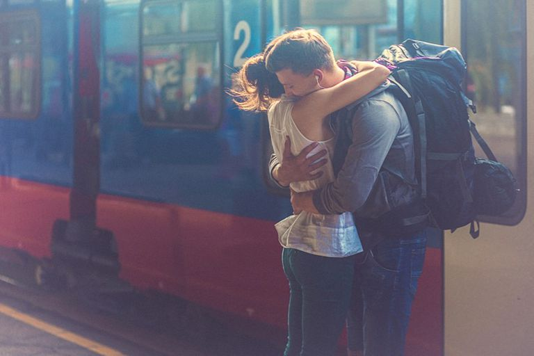 Man and woman hugging in front of subway train
