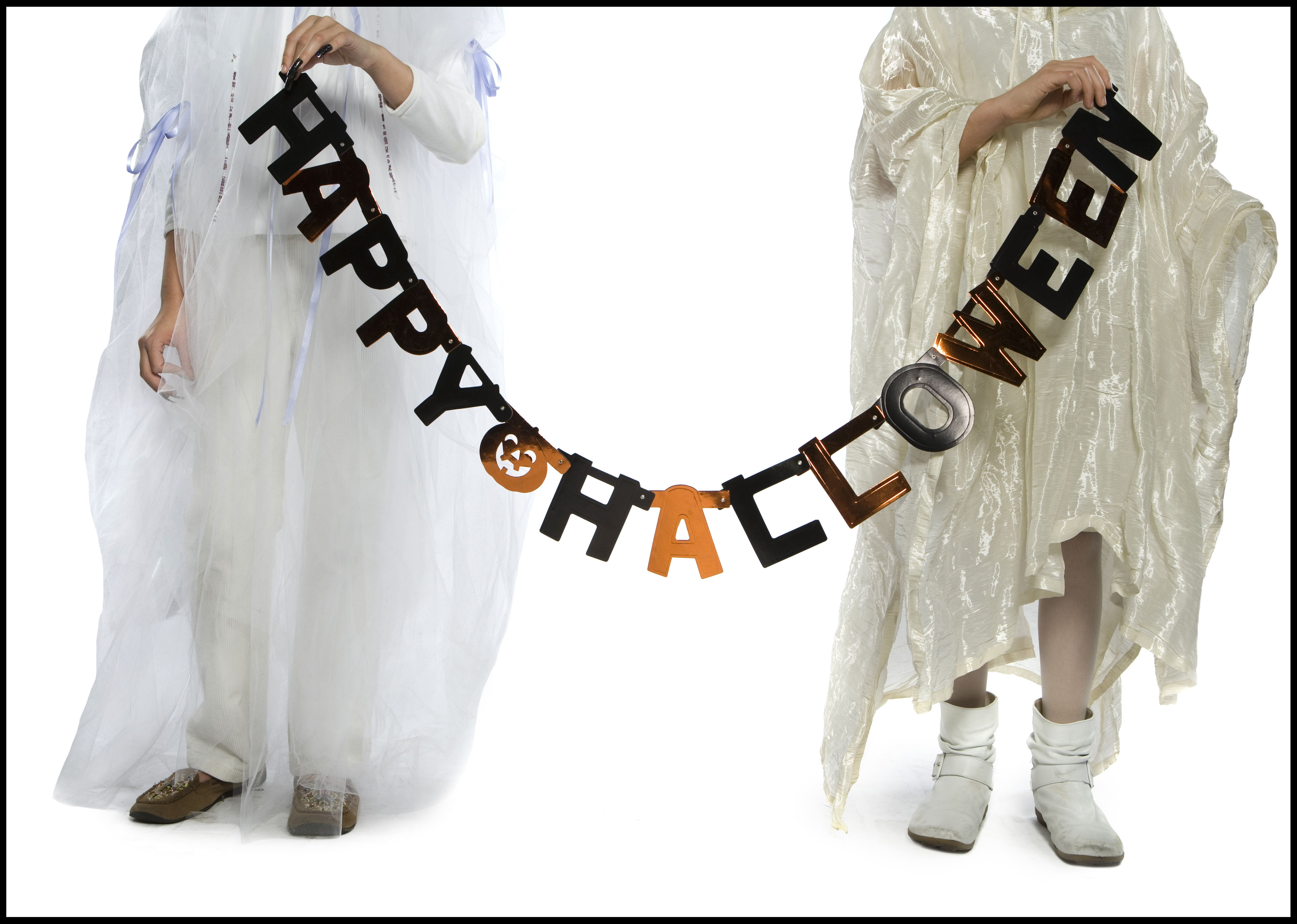 Boy and a girl holding a Halloween banner