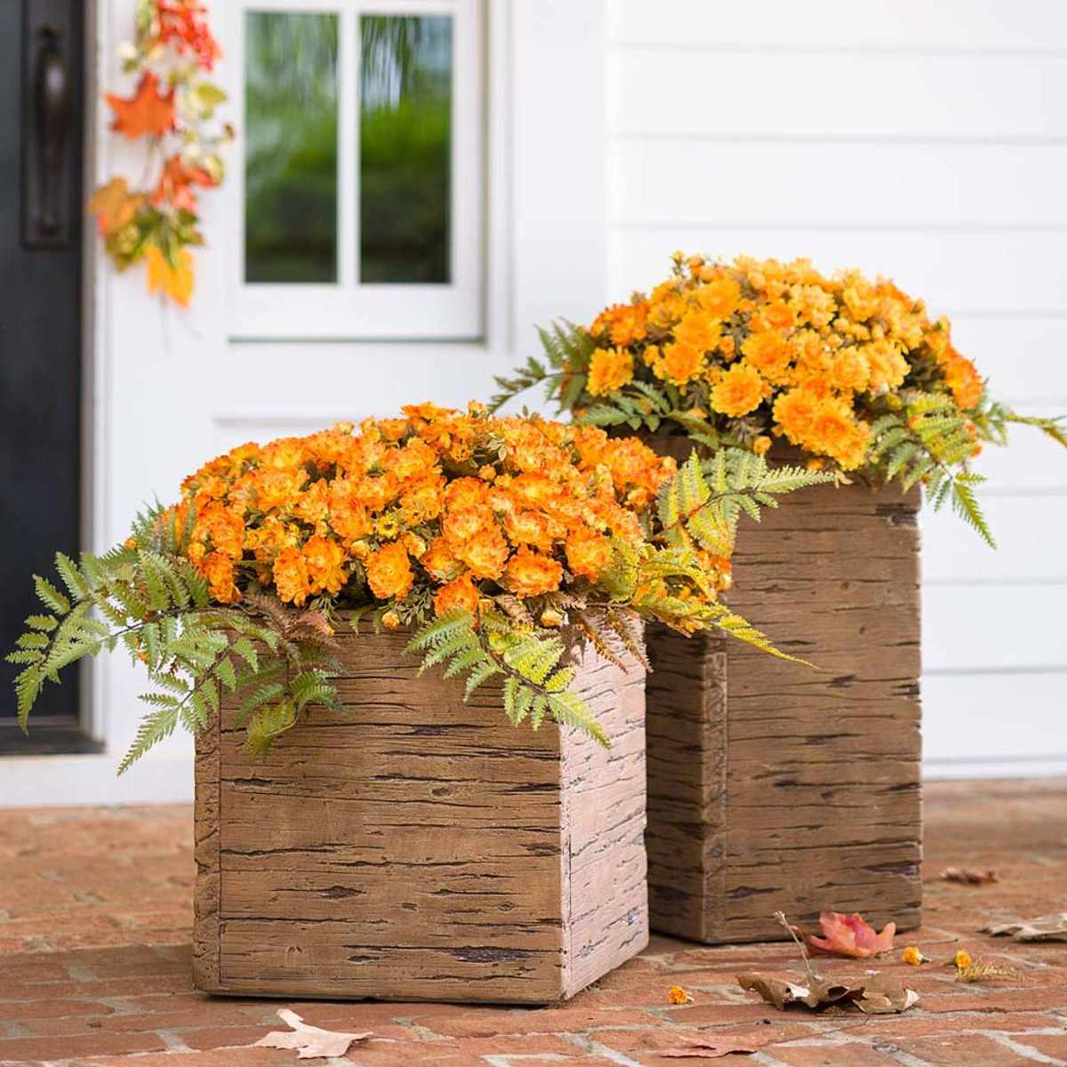 Two planters sold by Plow & Hearth full of fall flowers