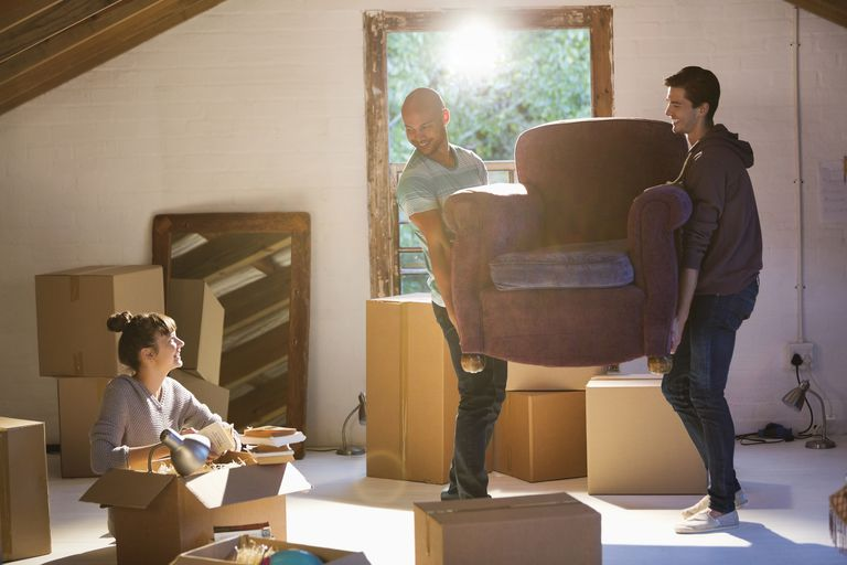 men moving furniture in to new house while woman unpacks boxes