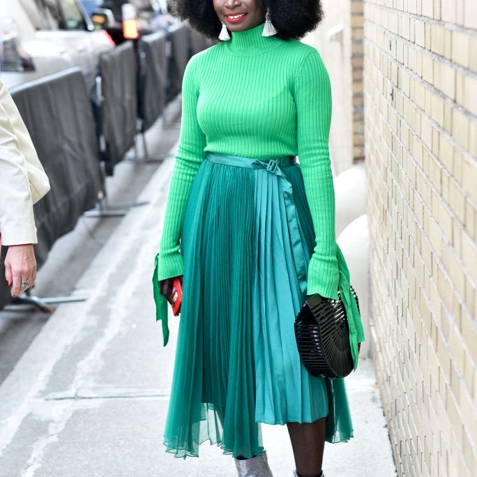 Woman wearing green top and green pleated maxi skirt