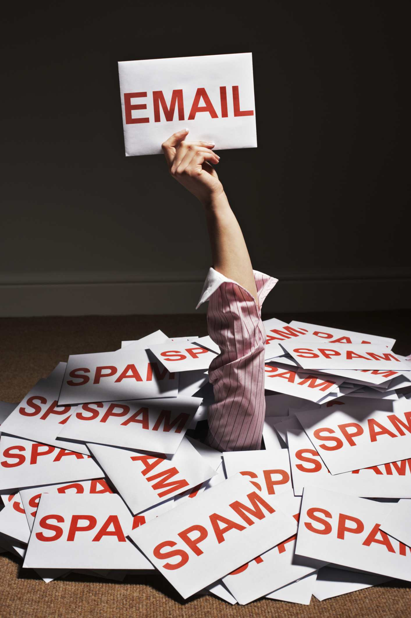 Image of a hand holding an email from a pile of spam.
