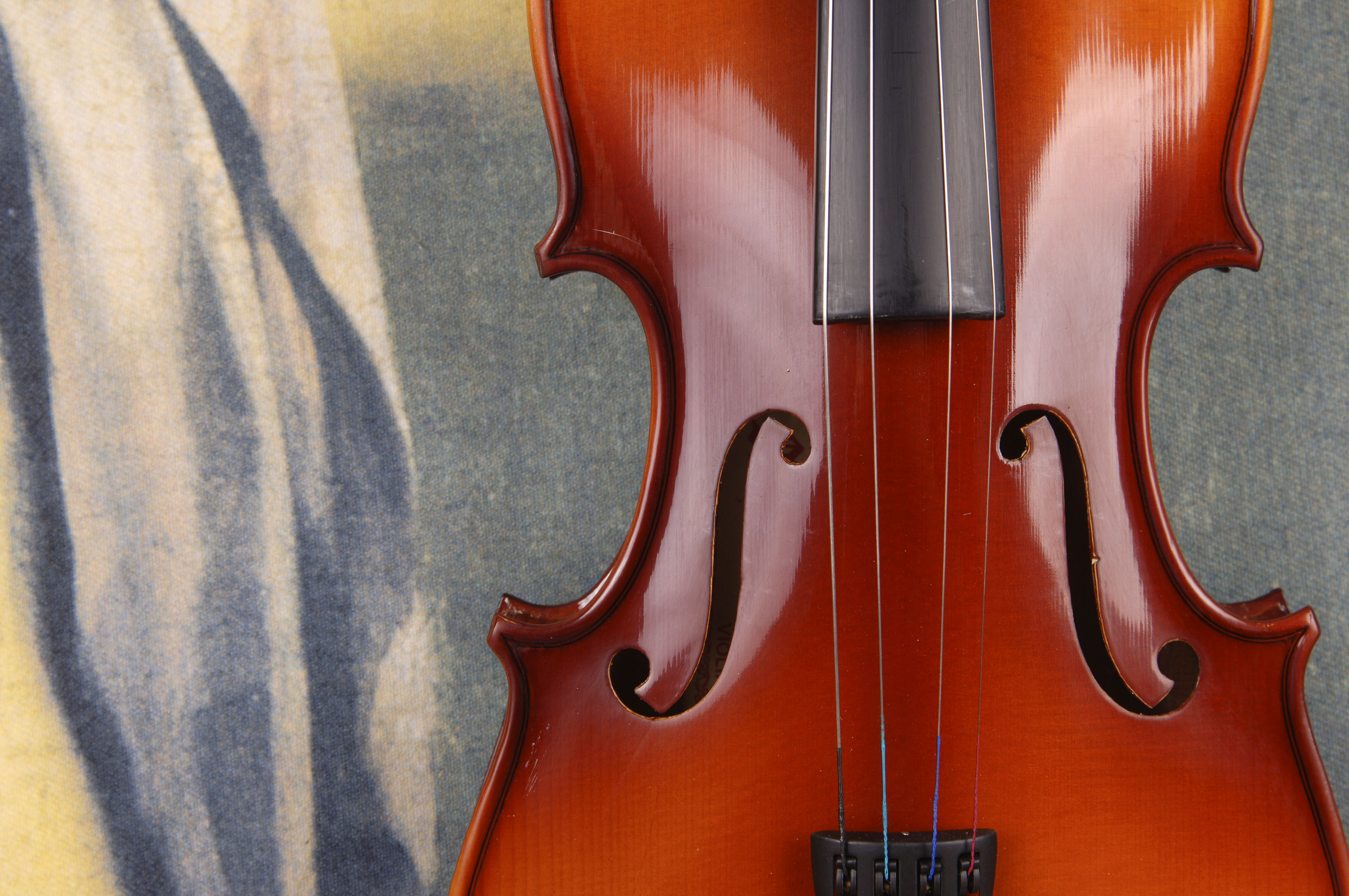 Violin against painted curtain, close-up