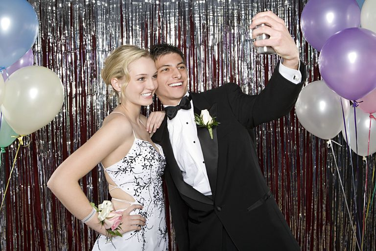 young man and woman taking selfie at prom