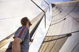 Man looking up at sailboat sails