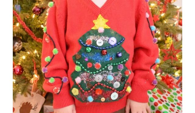 A child wearing an ugly Christmas sweater in front of a Christmas tree
