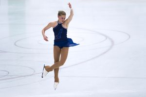 Female Skater Performing Jump During Figure Skating Competition