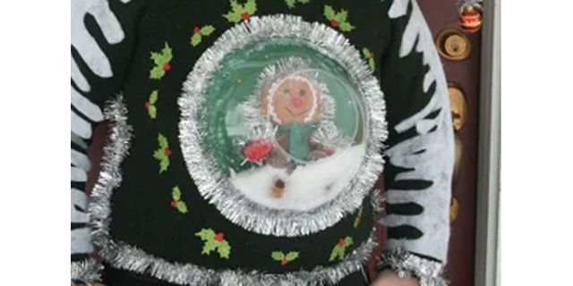 A man wearing an ugly Christmas sweater with a snow globe on the front