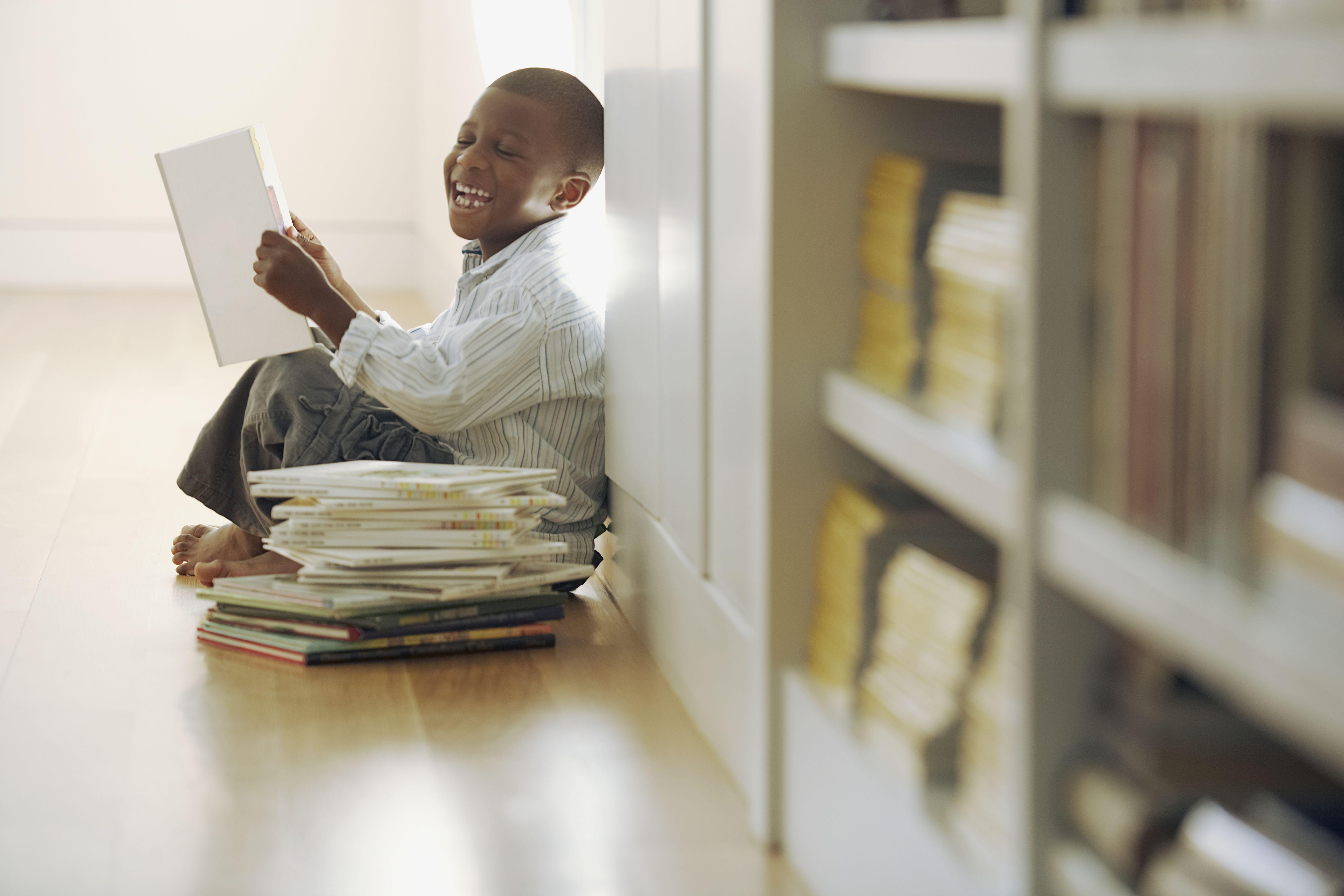 Young boy laughs at a storybook
