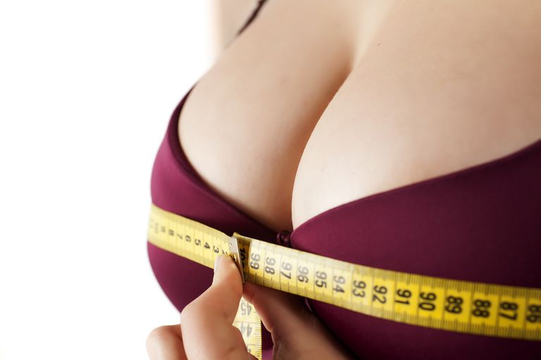 woman measured her breast with a measuring tape