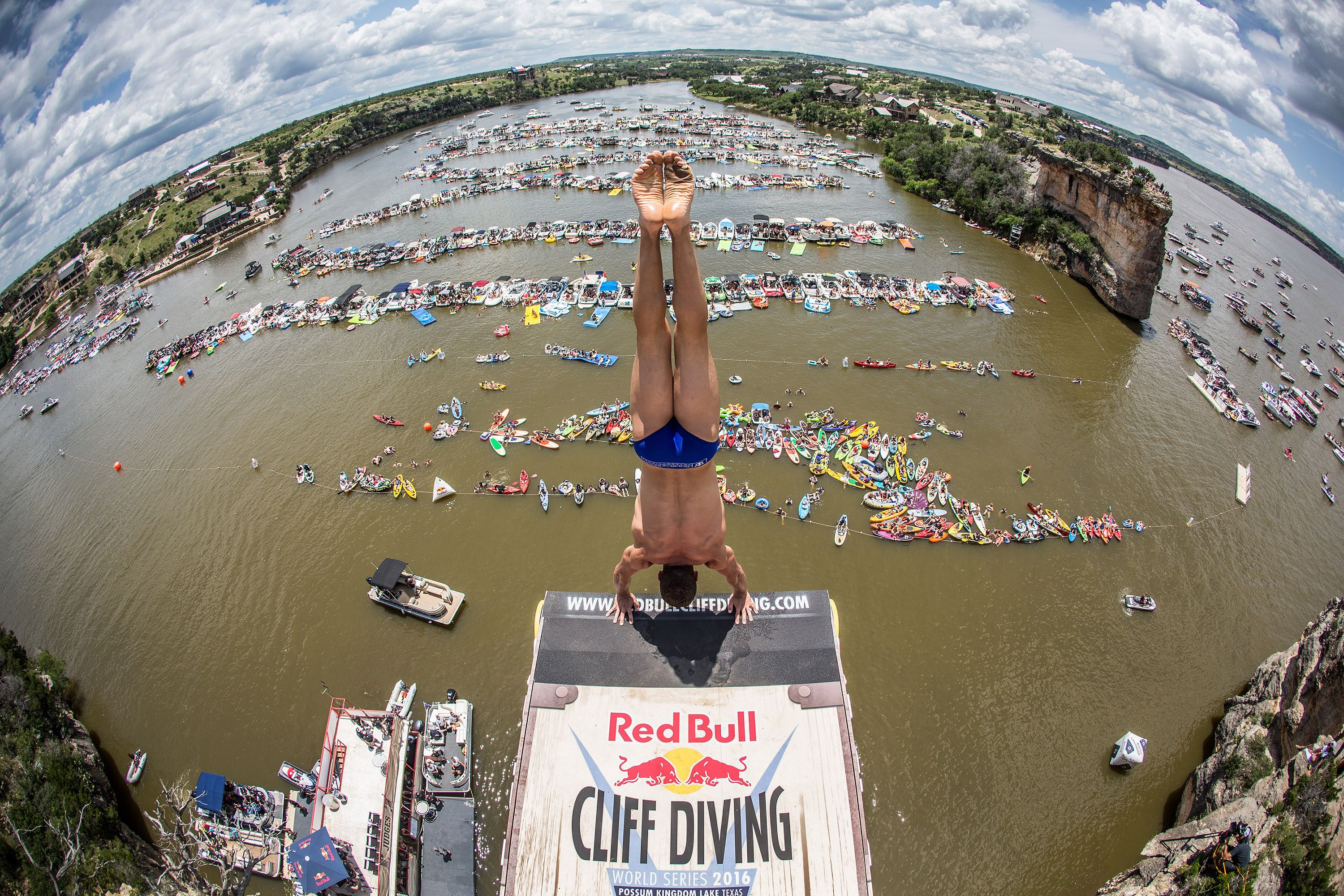 Man poised to take a handstand dive for the Red Bull cliff diving challenge.