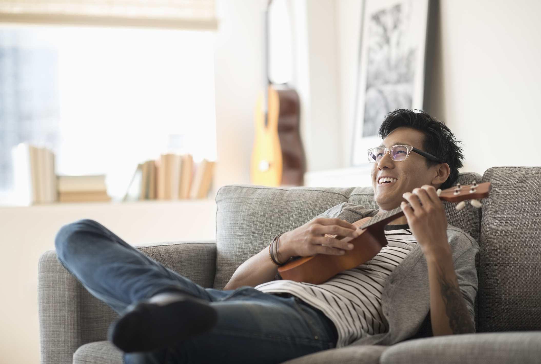 Jersey City, Man sitting on sofa and playing ukulele