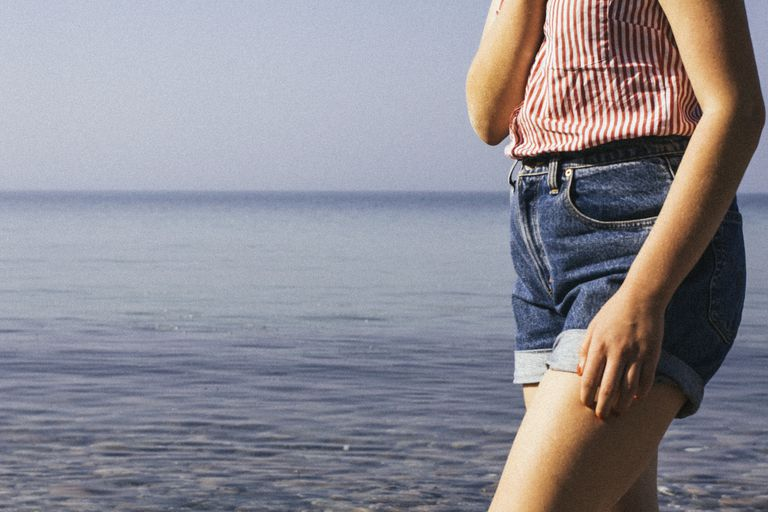 Woman in jean shorts by lake or ocean