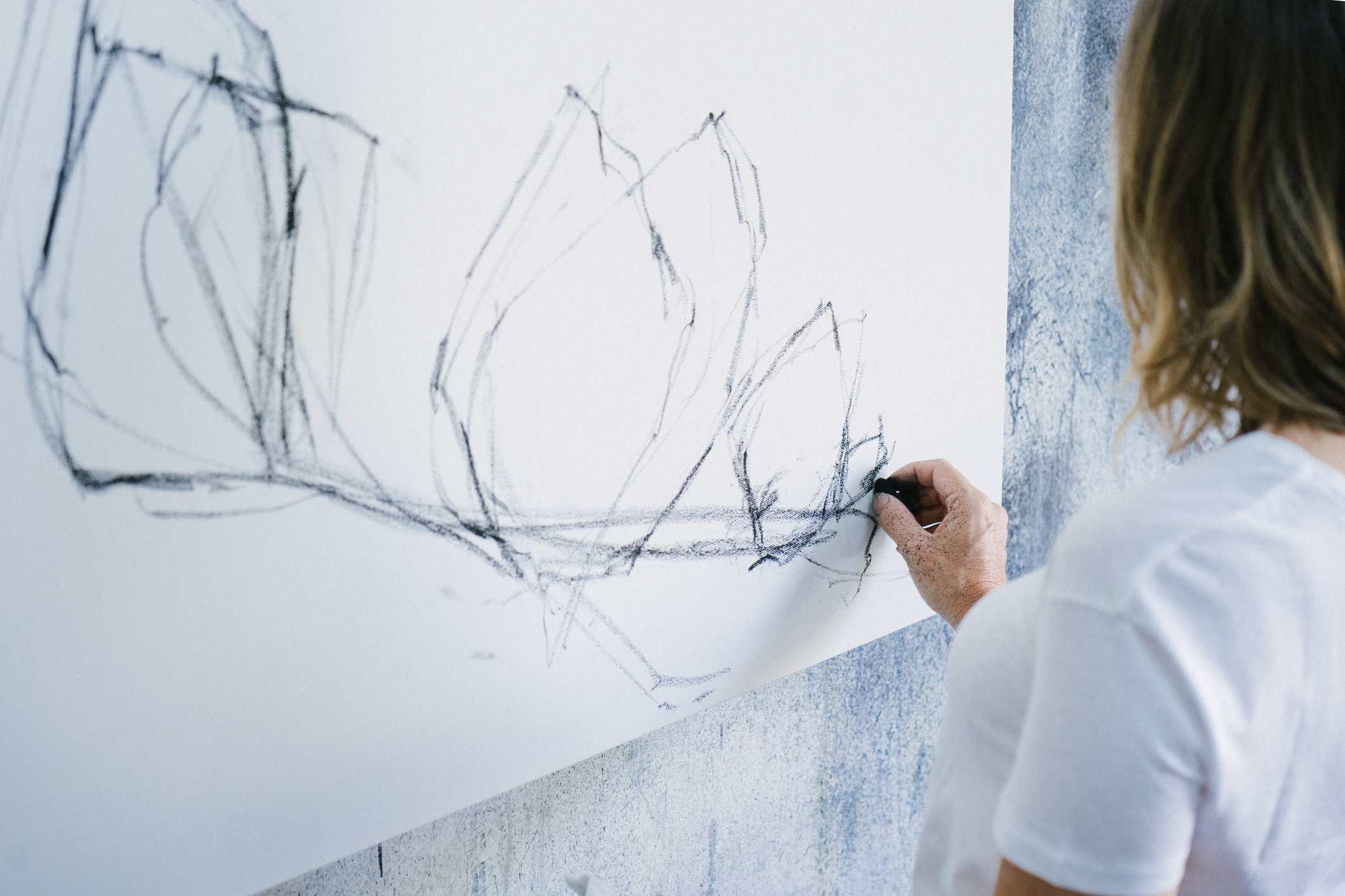 woman making a charcoal drawing